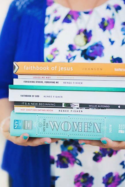 woman holding biblical books